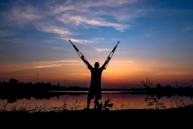 Gehandicapte man met krukken op zonsopgang achtergrond.