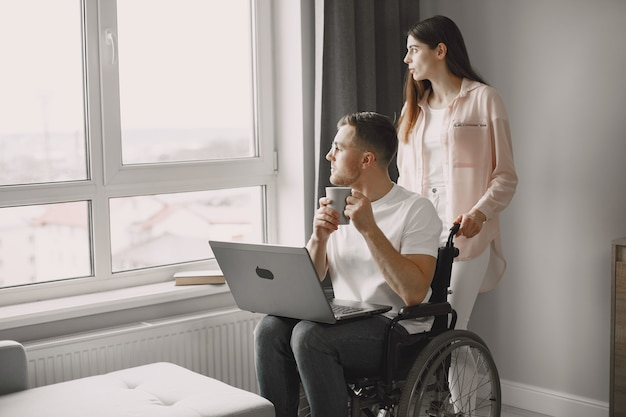 Gehandicapte man met laptop thuis en op afstand werken. de girlfrind juicht haar vriend toe.