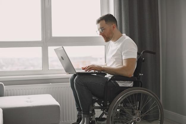Gehandicapte man met laptop. vrolijke knappe man thuis blijven en op afstand werken.
