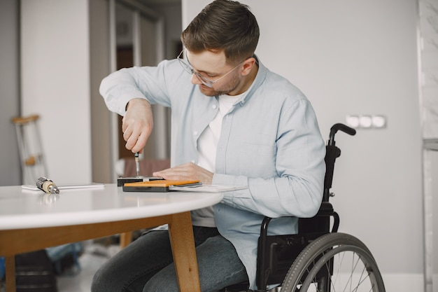 Gehandicapte man op rolstoel zoals repareren. thuis blijven, hobby's.