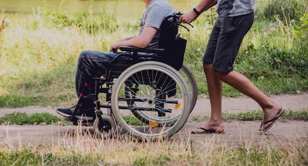 Gehandicapte man rusten op een camping met vrienden. rolstoel in het bos