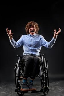 Gehandicapte man schreeuwen door wanhoop zittend op rolstoel geïsoleerd op zwarte muur. portret van gehandicapte man die handen opheft en zo hard mogelijk schreeuwt