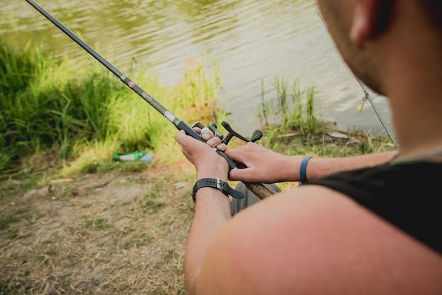 Gehandicapte man vissen op een meer. rolstoel. camping.