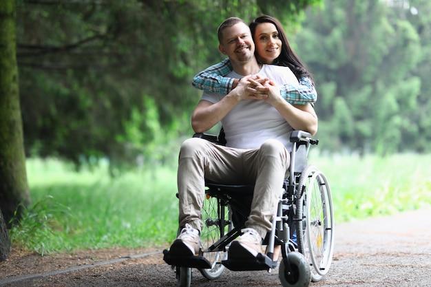 Gehandicapte man zit in rolstoel van achter knuffels mooie vrouw