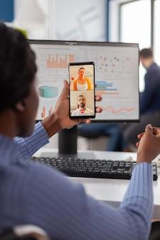Gehandicapte manager die op videocall praat met vrienden die mobiel werken bij een financieel bedrijf