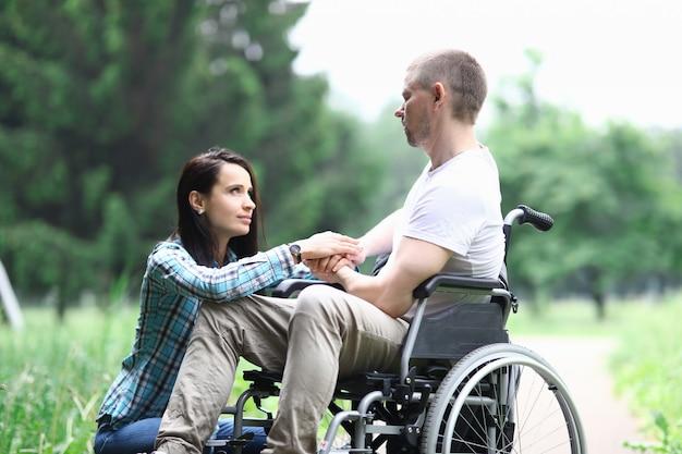 Gehandicapte mannelijke veteraan zit in rolstoel vrouw zit in de buurt