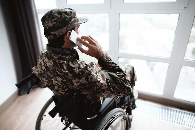 Gehandicapte militaire man praat telefoon in rolstoel
