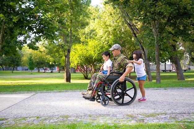 Gehandicapte militaire veteraan die met twee kinderen in park loopt. jongen zit op vaders schoot, meisje duwt rolstoel. veteraan van oorlog of handicap concept