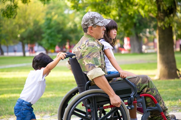 Gehandicapte militaire veteraan die met twee kinderen in park loopt. meisje zittend op vaders schoot, jongen duwen rolstoel. veteraan van oorlog of handicap concept