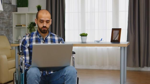 Gehandicapte ondernemer in rolstoel die vanuit huis op laptop werkt.