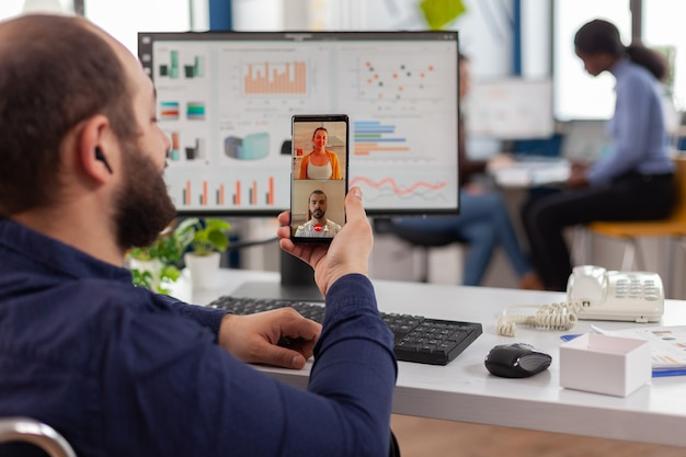 Gehandicapte ongeldige manager die op videogesprek praat met vrienden die een smartphone vasthouden die pauze neemt tijdens werktijd