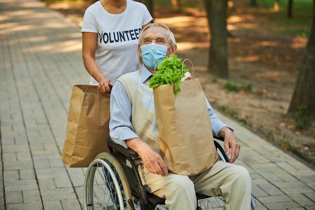 Gehandicapte oude man zit op de rolstoel terwijl hij een papieren boodschappentas met voedsel vasthoudt