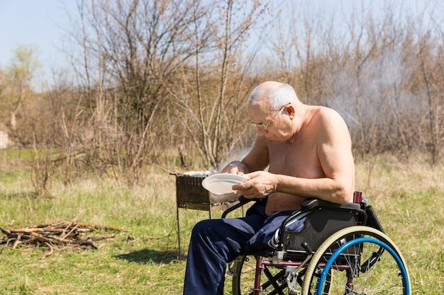 Gehandicapte oude man zonder shirt zittend op zijn rolstoel en zijn lunch eten in het park alleen op een zeer zonnige dag.