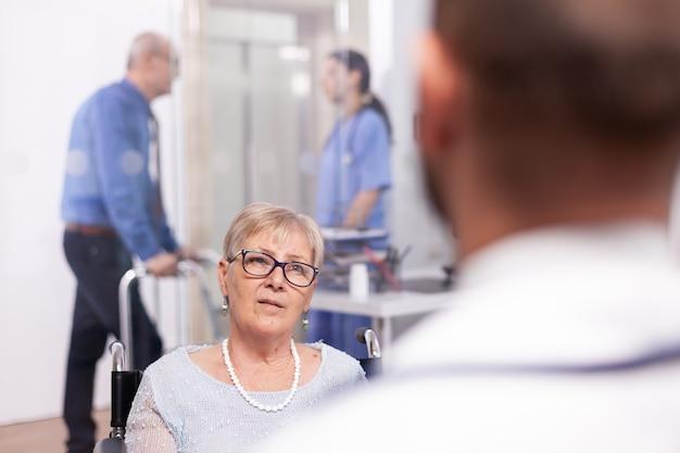 Gehandicapte oude persoon in rolstoel tijdens behandeling met geriater arts