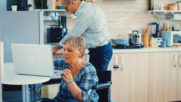 Gehandicapte oude vrouw in rolstoel die aan laptop in keuken werkt. verlamde gehandicapte oude bejaarde die moderne communicatie online internetwebtechnologie gebruikt.