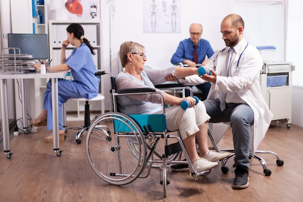 Gehandicapte patiënt krijgt hulp van fysiotherapeut