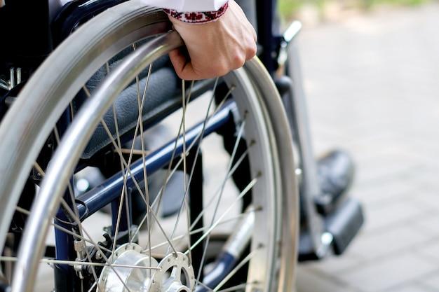 Gehandicapte persoon in een rolstoel op straat een jonge kerel in een rolstoel