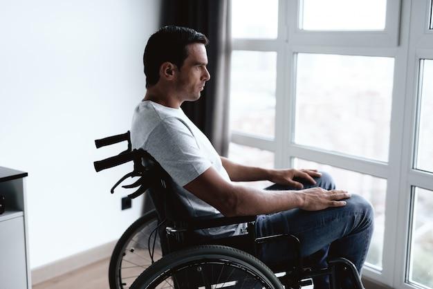 Gehandicapte persoon zit in rolstoel tegen raam.