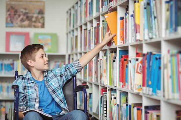 Gehandicapte schooljongen die boek in bibliotheek selecteert
