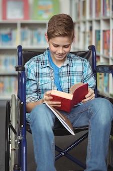 Gehandicapte schooljongen leesboek in bibliotheek