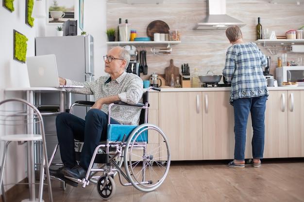 Gehandicapte senior man in rolstoel die op laptop in de keuken werkt terwijl de vrouw een heerlijk ontbijt voor hen beiden bereidt. man met behulp van moderne technologie tijdens het werken vanuit huis.