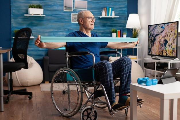Gehandicapte senior man in rolstoeltraining met elastische band die lichaamstraining uitoefent en herstellende is na een invaliditeitsongeval bij het kijken naar strech-video op televisie