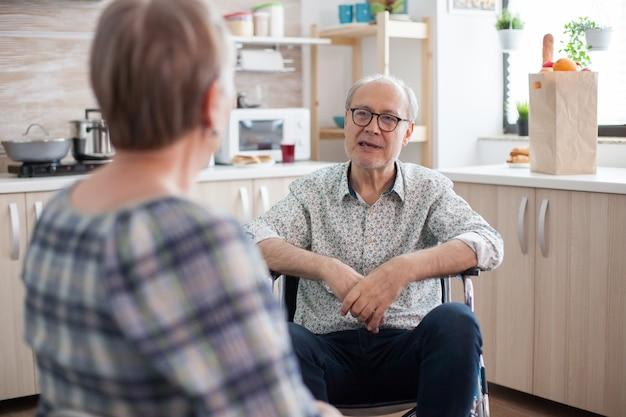 Gehandicapte senior man praten met vrouw in de keuken. bejaarde die een gesprek met echtgenoot in keuken heeft. leven met een gehandicapte met een loophandicap