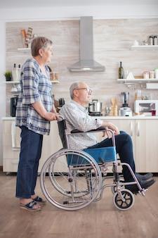 Gehandicapte senior man zit in een rolstoel in de keuken en kijkt door het raam. leven met gehandicapte. vrouw helpt man met een handicap. bejaard paar met gelukkig huwelijk.