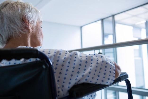 Gehandicapte senior patiënt op rolstoel in ziekenhuisgang in het ziekenhuis