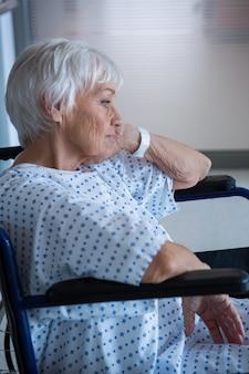Gehandicapte senior patiënt op rolstoel in ziekenhuisgang