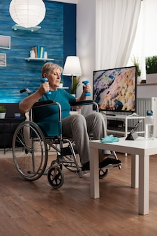 Gehandicapte senior vrouw in rolstoel die zich uitstrekt van de armspieren die lichaamsweerstand uitoefenen
