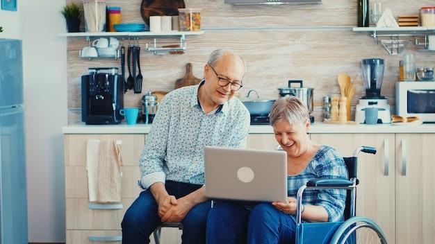 Gehandicapte senior vrouw in rolstoel zwaaien tijdens een videoconferentie die naast haar man zit. verlamde gehandicapte oude oudere vrouw en haar man op online oproep, met behulp van moderne communicatietechnologie.