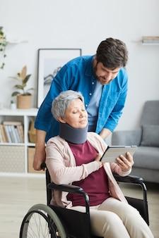 Gehandicapte senior vrouw in verband zittend in een rolstoel en iets op tablet pc tonen aan de man