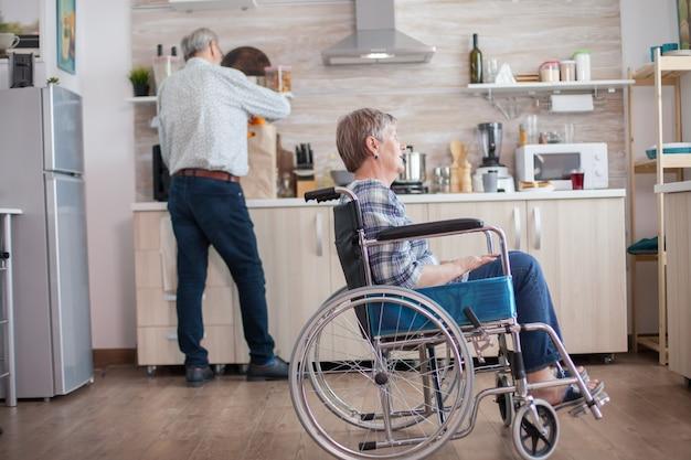 Gehandicapte senior vrouw zit in een rolstoel in de keuken en kijkt door het raam. leven met gehandicapte. echtgenoot helpt vrouw met een handicap. bejaard paar met gelukkig huwelijk.