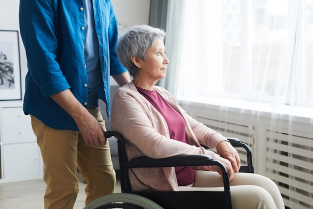 Gehandicapte senior vrouw zittend in een rolstoel en kijkt door het raam met verzorger in de buurt