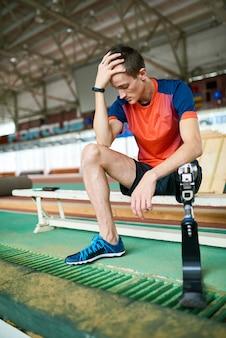 Gehandicapte sportman zittend op bankje in de sportschool
