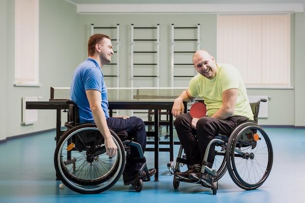Gehandicapte volwassen mannen lachen na het spelen van tafeltennis