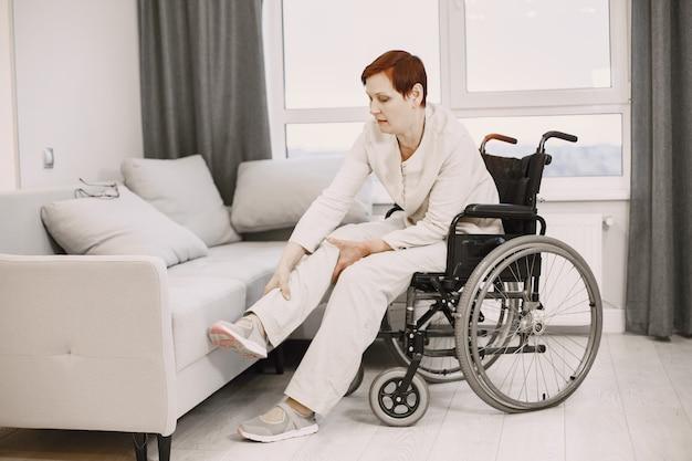 Gehandicapte vrouw. dagelijkse routine. de vrouw gaat in rolstoel zitten.