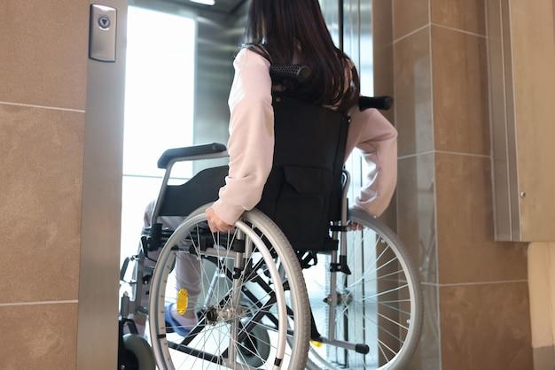 Gehandicapte vrouw in rolstoel die achteraanzicht van de lift binnengaat