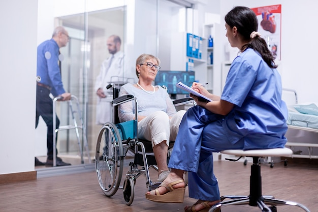 Gehandicapte vrouw in rolstoel die de vragenlijst van de verpleegster beantwoordt tijdens medisch onderzoek in de ziekenhuiskamer