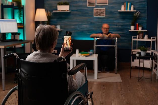 Gehandicapte vrouw in rolstoel die videogesprektechnologie gebruikt