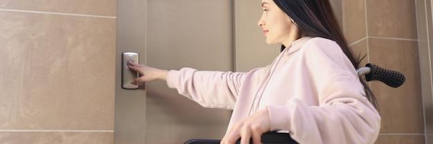 Gehandicapte vrouw in rolstoel drukt op belknop
