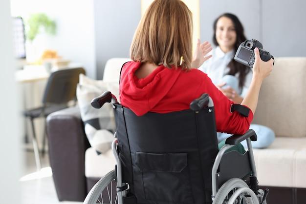 Gehandicapte vrouw in rolstoel fotografeert meisjesappartement. werk voor het concept van positieve emotie mensen.