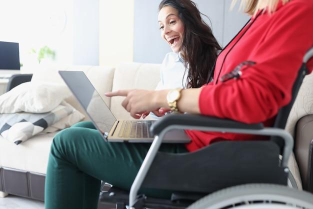 Gehandicapte vrouw in rolstoel met een laptop op haar knieën laat haar vrolijke vriendin haar prestaties op het werk zien