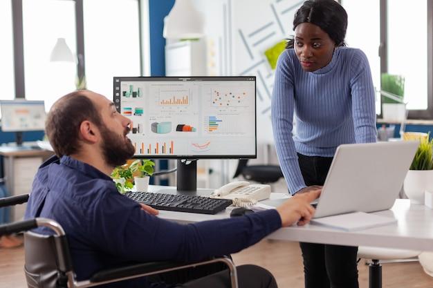 Gehandicapte zakenman en werknemer werken samen aan financieel project voor startend bedrijf