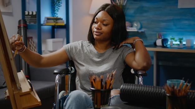 Gehandicapte zwarte vrouw die vaasontwerp tekent bij kunststudio