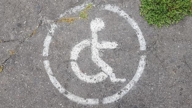 Gehandicaptenparkeersymbool. gehandicapte baai gemarkeerd met een persoon in een rolstoelbord op grijs asfalt op een grote parkeerplaats close-up. uitzicht van boven.