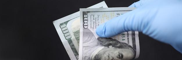 Gehandschoende hand houdt honderd dollarbiljet vast. geld overgedragen ziekten concept
