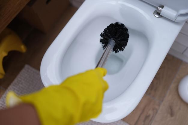 Gehandschoende hand maakt toilet met borstelclose-up schoon