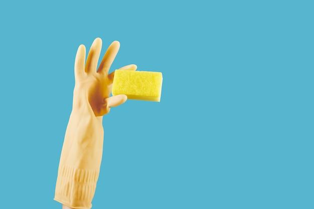 Gehandschoende hand met keukenspons